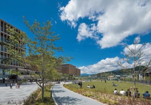 「常葉(とこは)大学静岡草薙キャンパス」(2018年)を南東から見る。敷地の周囲に塀がないオープンなキャンパス。建物の内外をつなぐ部分は、地域の人々を含めた皆の居場所として重要な役割を担う(写真:エスエス)