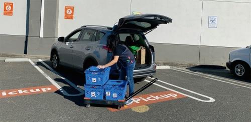 (c)トランクに荷物を載せる従業員