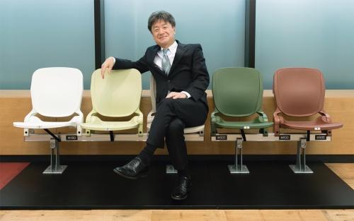 梓設計の杉谷文彦社長。オフィス入り口には、国立競技場の観客席の原寸大模型を展示している(写真:的野 弘路)