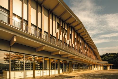 木梁(欧州アカマツ)と木ルーバー(スギ)の並ぶ西面の外観。屋根はカラーステンレス、一部保水セラミックパネル+植栽。外壁は高耐久樹脂含浸積層材(スギ)、アルミパネル、防水形複層塗材E。外まわり建具はアルミサッシ、ステンレスサッシ、スチールサッシ(写真:川澄・小林研二写真事務所)