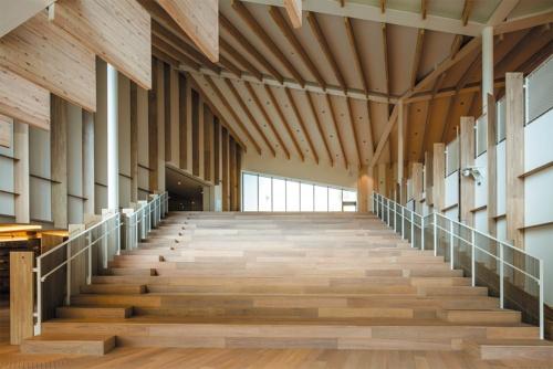 吹き抜けの大階段のあるエントランスホール。右手に滑り台を併設している。床はフローリング(オーク)、壁は EP塗装、天井は木梁現し、不燃木シート、岩綿吸音板(写真:川澄・小林研二写真事務所)