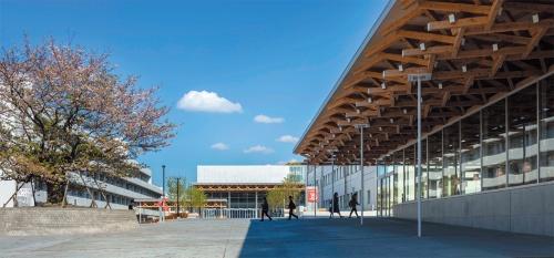 正門側からシンボルロードの向こうに立つ音楽ホール棟(新築)を見る。右手前が図書館(同)(写真:小川重雄)