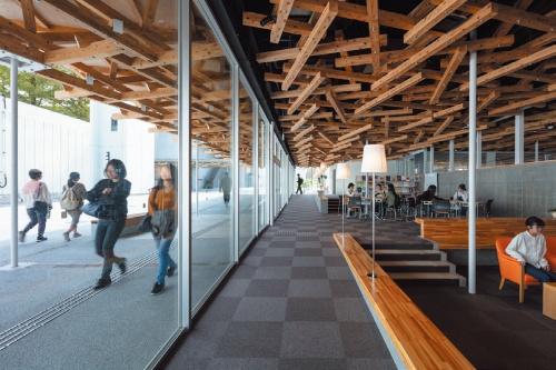 図書館の開口部側。内外を横断する木屋根や、勾配のある微地形に合わせた設えによって、ランドズケープに溶け込む居場所をつくった(写真:小川重雄)