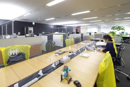 オカムラのオフィスの様子。2020年6月18日に撮影した。机の上にパネルを設置するほか、使用しない席にカバーをかぶせて座席数を減らしている。オカムラによると、2020年5月中旬以降、飛沫飛散を防止するパネルの引き合いがあり、数万枚を受注している(写真:安川 千秋)
