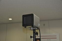 16人同時にAI顔認証と検温ができるホール型のカメラとディスプレー(右)。カメラが撮影するエリア内に恒温発生装置(左)を設置する。販売価格は税抜き298万円から(写真:日経クロステック)