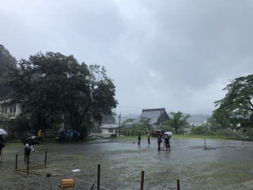 木造応急仮設住宅15戸の建設用地となる人吉市の人吉城跡の駐車場内で、雨が降る中、作業員が地縄を張って配置などを決めている様子(写真:KKN)
