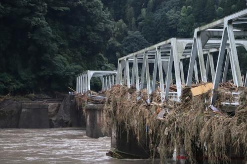 人吉市内の西瀬橋を右岸側の上流寄りから眺めたところ。写真奥から2番目の橋桁が流失し、橋には多くの流木や草が絡みついている(写真:水源地環境センター)