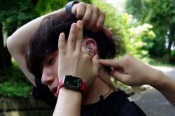 耳にはイヤホン型の体温計を装着。鼓膜からの赤外放射を基に、深部体温を測定する。 データはリアルタイムで取得できる(写真:日経クロステック)