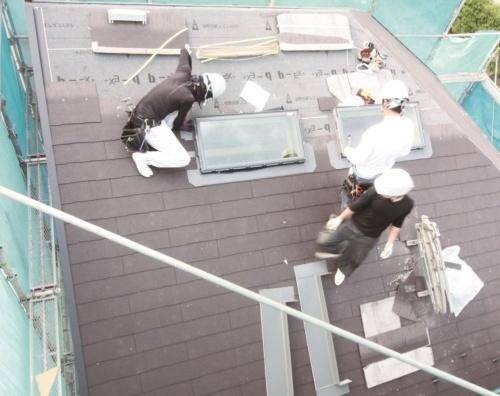 """屋根の化粧スレートを施工する外国人技能実習生。実態として、人手不足の""""穴""""を補う存在だった(写真:大菅 力)"""
