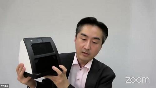 顔認証付きカードリーダーを提示して説明する大竹雄二室長