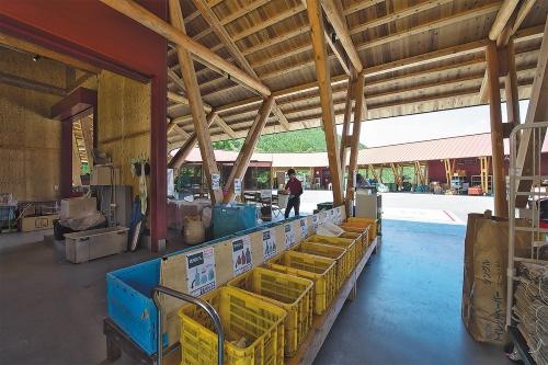 ごみステーションには職員が常駐し、町民の分別を手伝う。ごみの入れ物にはそれぞれ、そのごみをリサイクルすると町にお金がいくら入るか、出ていくかが表示されている(写真:生田将人)