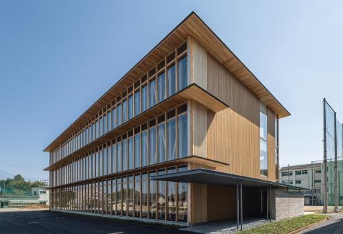 敷地は小高い丘の上にあり、北側に住宅地が広がる。木造校舎が町の風景に寄与することを狙い、北面は外からガラス越しに柱と筋交いが見えるようにした。内部は、1日を通して明るさが安定している北側に教室と実習室を配置した(写真:艸建築工房)