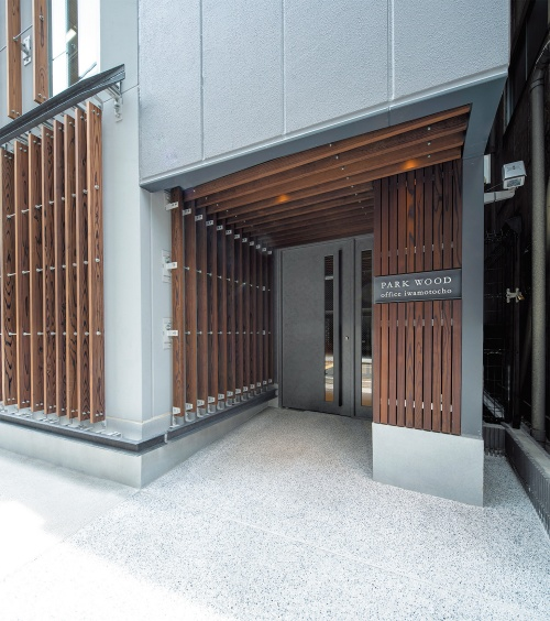 1階のエントランス。外壁のALC(軽量気泡コンクリート)版に製造時に埋め込んだボルトファスナーで木ルーバーを固定した(写真:三菱地所設計)