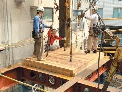 CLTパネルを鉄骨躯体に載せて、コンクリートを打設して一体化する(写真:三菱地所設計)