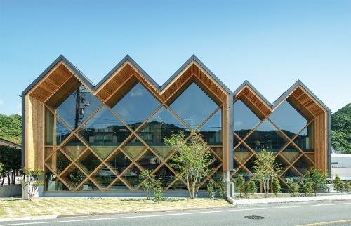 国道に面して5つの折板屋根が並ぶ南面の全景。折板屋根は、国内で製造できる最大寸法の幅3m、長さ12mのスギのCLTで構成している。厚さは120mm。CLTを持ち出した軒の深さは約1.5m(写真:銘建工業)