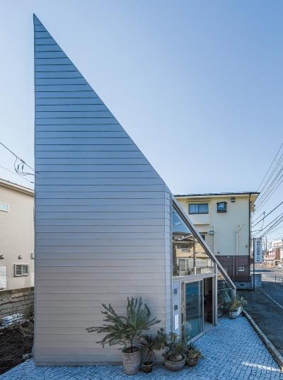 巨大な三角形に見える住宅。玄関周りはガラス張りで、中のアトリエ・ギャラリーが外から見える(写真:高栄智史)
