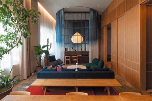 2020年2月開業の「K5」4階にある客室「ロフト」。80m<sup>2</sup>の空間にキングサイズのベッドやオリジナルのソファ、ダイニングテーブルなどを配置。4.5mある天井高を生かした、ゆったりとした空間だ。右手奥にバスルームがある(写真:山本 育憲)