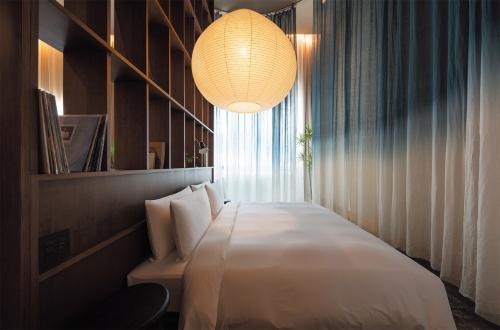 「K5」4階にある客室「ロフト」のベッド周り。テレビはなく、キュレーターの選んだ本を置いている(写真:山本 育憲)