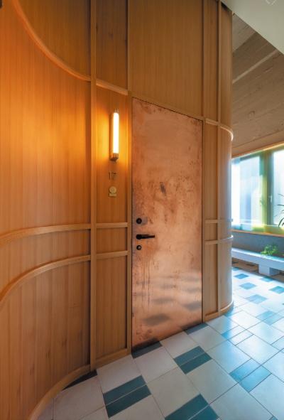 「K5」4階の廊下。曲げ木を思わせる壁面処理と銅板を用いた客室扉(写真:山本 育憲)