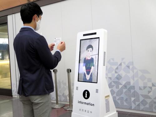 日本航空(JAL)とパナソニックが羽田空港で実施した、アバターによる遠隔接客の実証実験の様子。搭乗客が搭乗券をアバターに向かって見せている