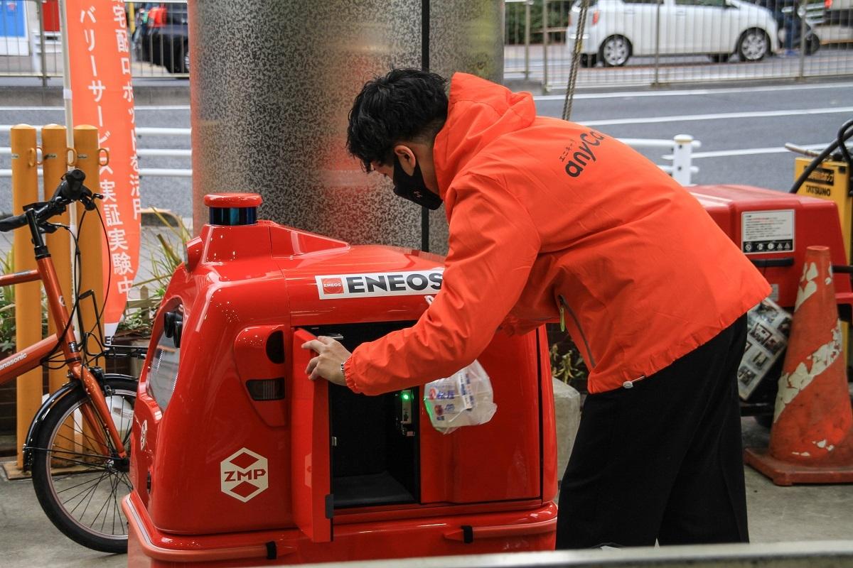 図1 給油所を拠点にした自動配送サービス実証実験 無人宅配ロボットの荷積みや充電場所として東京・中央の給油所「ENEOS月島SS」を活用する。配送システムはENEOSとエニキャリ(東京・千代田)が共同で手掛け、ZMP(東京・文京)製の車両を使って配送する。(出所:ENEOSホールディングス)