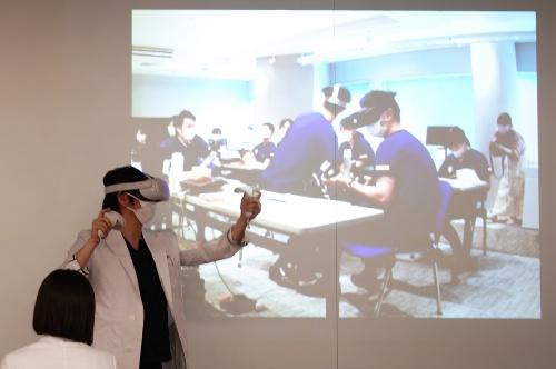 図1 ソフトバンク本社(東京都港区)にいる指導医が、大阪市の会場にいる12人の若手歯科医を対象に技術指導した(撮影:日経クロステック)