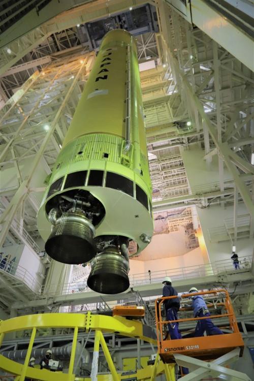 2021年2月初旬から、種子島宇宙センター吉信射点の機体組立棟(VAB)では、H3の点検用組み立てが進められた。横倒しで搬入された第1段機体をVABのクレーンでつり上げて直立させる。第1段エンジンのLE-9は開発が続いていたため、装着されているのは燃焼試験に使われた試験用のエンジン。(出所:JAXA)