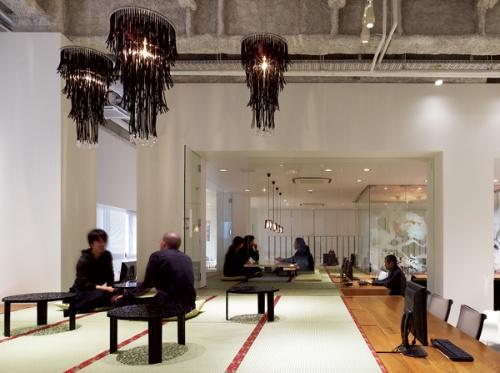 2階のオフィス。畳とシャンデリア、ガラス間仕切りにちゃぶ台。キッチュにならないようにうまくバランスを取っている (写真:阿野 太一)