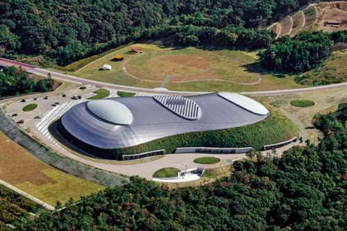 西側上空から見たビーンズドーム。非対称形のユニークな平面形の内部にはテニスコート9面が配されている(写真:スカイフォト)