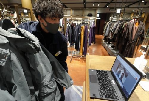 三越伊勢丹リモートショッピングによる接客の様子。販売員はチャットやビデオ通話機能を使って顧客とやり取りする