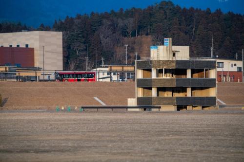 盛り土の手前にある震災遺構の米沢商会のビル。2021年2月10日撮影(写真:村上 昭浩)