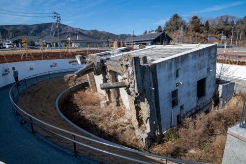 横倒しになった旧女川交番。奥には駅前に整備された商業施設「シーパルピア女川」などがある。2021年2月撮影(写真:村上 昭浩)