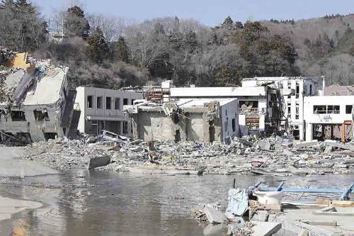 震災直後の旧女川交番。一帯は地盤沈下で水没したままになっていた。左隣にも横転した建物がある。女川町は2011年当時、旧女川交番と女川サプリメント、江島共済会館の3つの建物を震災遺構の候補として挙げていた(写真:日経アーキテクチュア)