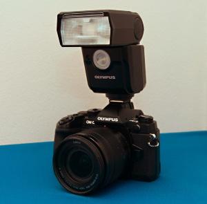 連載で使用するミラーレス一眼カメラ。センサーサイズは4/3型、有効画素数は1628万画素。レンズは焦点距離が12~60mmのズームレンズを使用した。撮影環境がやや暗く鮮明な写真が撮影しにくかったことから、クリップオンストロボを併用している(撮影:日経クロステック)