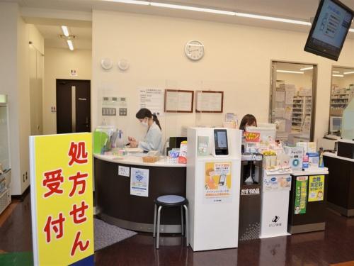日本調剤駿河台薬局。受付の脇に顔認証付きカードリーダーが設置されている。患者が操作しやすい高さで、両脇からののぞき込みを防ぐ専用の台を独自に用意した
