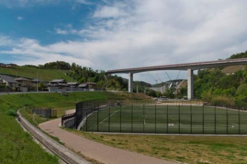 ダム建設工事にあわせて整備されたグラウンド(手前)と桑原大橋(府道46号)の向こうにダムを望む(写真:生田 将人)