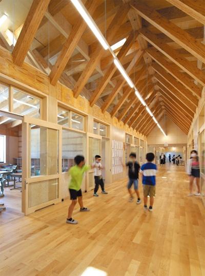 教室棟の3階廊下。構造用LVLを用い、150mm×350mmの登り梁(千葉県産スギ)を150mm×150mmの方杖(信濃町産カラマツ)で支持する屋根架構としている(写真:安川千秋)