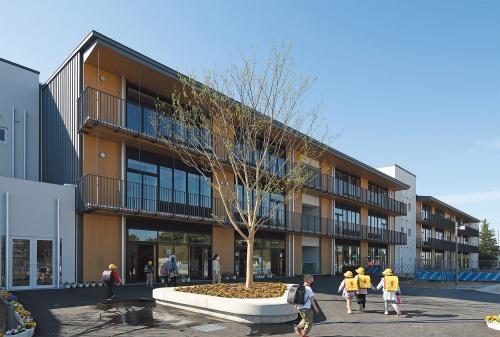 教室棟(北棟)を北側から見る。軒下やバルコニー下面、外装材などは木質の素材で仕上げ、木の表情を感じることができる外観とした(写真:安川千秋)