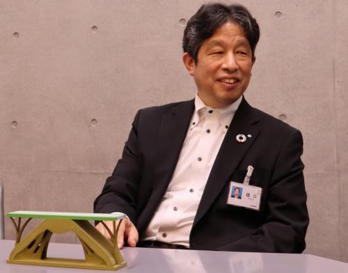 清水建設執行役員土木技術本部長の樋口義弘氏。1959年生まれ。84年4月に清水建設に入社、土木本部土木開発部に配属。2011年4月に土木技術本部バックエンド技術部長、16年4月に土木技術本部副本部長、19年4月から現職。20年4月に土木教育委員長に就任。手前の模型は、20年9月~21年3月に実施した設計コンテストで「2班」の新入社員が3Dプリンターで製作した。耐荷力とプレゼンテーション内容で高い評価を得た(写真:日経クロステック)
