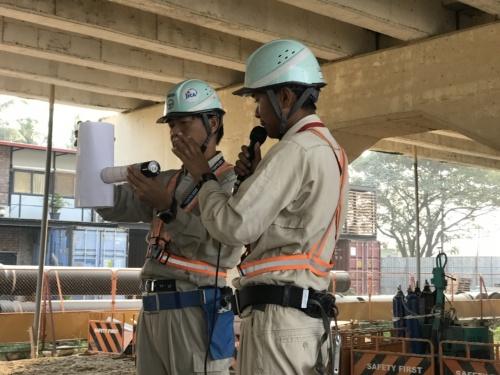 ミャンマーの現場の朝礼で、推進管が水圧で立て坑側に戻る推進工事のバッキング現象を説明している様子。模型は小野寺氏が作った(写真:戸田建設)