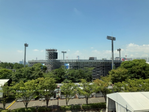 大会直前の日の丸がたなびくビーチバレーボール競技会場。四方を観客席に囲まれた競技会場で、テレビ中継に映し出された東京の都市景観は、隣接するホテルの外観がわずかに見えただけだった(写真:山嵜 一也)
