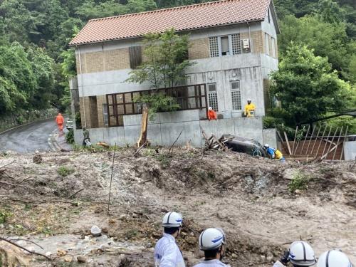 長崎県雲仙市小浜町で発生した土砂崩れの現場。写真に映る赤い屋根の住宅の前を左から右に土砂が流れた。2021年8月16日午前10時撮影(写真:雲仙市)