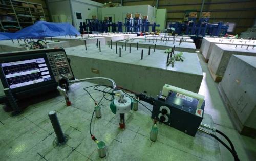 日本建築あと施工アンカー協会の技術センターで、あと施工アンカーの供試体を製作。手前に見えるのが「電磁パルス法」の装置(写真:日経コンストラクション)