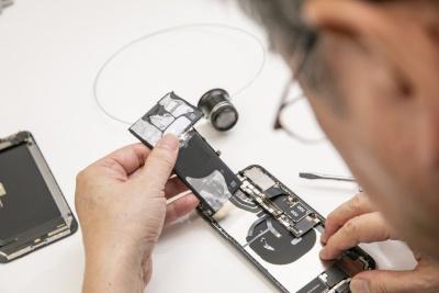 iPhone XS Maxの電池を取り外す。粘着テープが無線給電のコイルを避けるように貼られていた