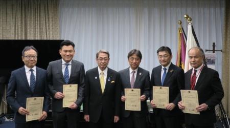 2019年4月10日の交付式では、石田真敏総務大臣(左から3人目)がNTTドコモ、KDDI、沖縄セルラー電話、ソフトバンク、楽天モバイルの経営トップに認定書を交付した