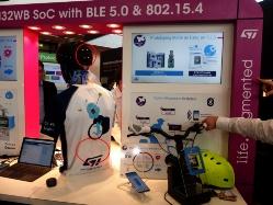 ブースでのデモンストレーション。二輪車のブレーキを操作すると、背中とヘルメットのLED(赤丸で囲んである)が光るという内容(写真左)。ヘルメット、Tシャツ、ハンドルの3カ所にSTM32WBが取り付けられていて(赤丸で囲んである)、Bluetoothで通信する(写真右)。ハンドルのチップを中心としたスター型で接続。日経 xTECHが撮影。