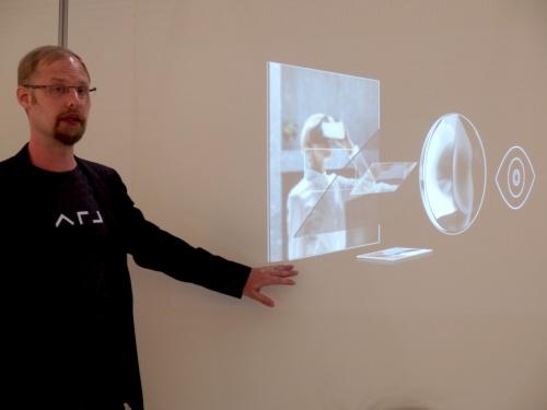 登壇したUrho Konttori氏。同社の技術のポイントを説明。全体は低解像度にし、目線がある2度の視野だけ高解像度にすることで、実質的に高解像度の映像を低消費電力で見せられるという。日経 xTECHが撮影