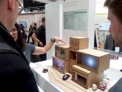 左は家電を対象にしたOPTIGA Trust Xのデモの様子。複数の家電製品を結びセキュアーなスマートホームを実現することを訴えている。右はOPTIGA Trust Xを組み込んだ独KEWAZO社の産業用ロボットのデモの様子。日経 xTECHが撮影
