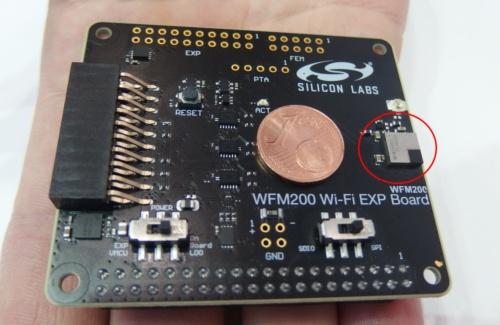 評価ボード上のWiFiトランシーバーモジュールの「WFM200」(赤丸で囲んでいるパッケージ)。その左は1ユーロ・セント・コイン。日経 xTECHが撮影。