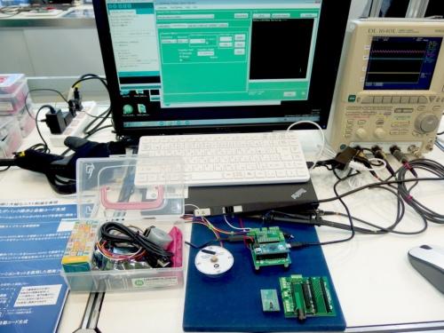 左手前の透明ボックスにまとまっているのが今回の開発キット。ボックスの左端の箱には「Arduino Micro」が入っている。中央の青色の板の中央(ノートPCの手前)が今回のキットのベースボードに、モーター駆動IC「LV8548MC」を載せたモジュール「LV8548MCSLDGEVB」とArduino Microが挿したもの。中央後ろが、GUIツールの稼働画面。日経 xTECHが撮影
